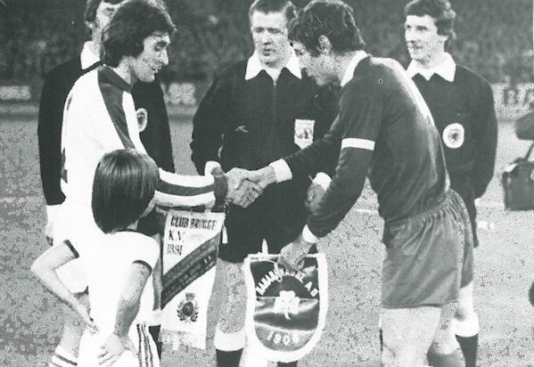 Στη φωτογραφία οι δύο αρχηγοί στον αγώνα της Κλαμπ Μπριζ με τον Παναθηναϊκό, το 1977.ΟΓιώργος Γονιός ανταλλάσει λάβαρα με τον Άλφονς Μπάστενς που έφυγε από την ζωή το 2008 σε ηλικία 61 χρόνων.
