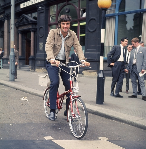 29th July 1968: Manchester United star George Best riding a bike down the street in London after receiving a six month driving ban from a Manchester court. (Photo by Ian Tyas/Keystone/Getty Images)