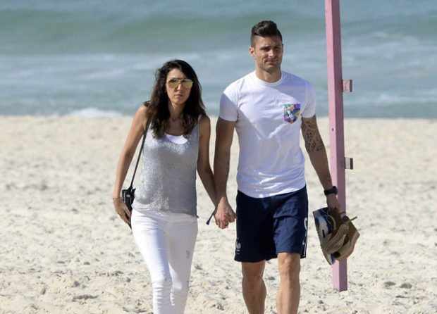 France's forward Olivier Giroud and his wife Jennifer Giroud walk on a beach in Rio de Janeiro during the 2014 FIFA World Cup football tournament on June 26, 2014. AFP PHOTO / FRANCK FIFE