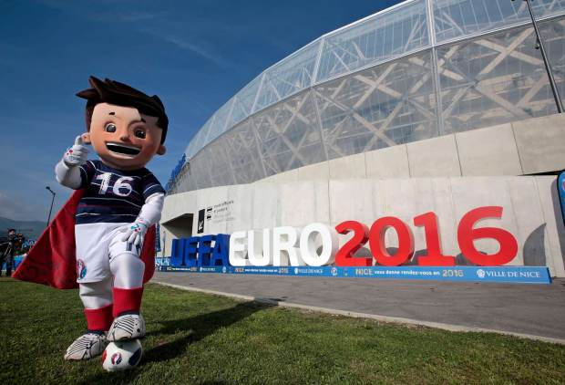 The official Mascot, Super Victor, for the upcoming Euro 2016 soccer championship, poses in front of the UEFA Euro 2016 logo at the Allianz Riviera stadium in Nice