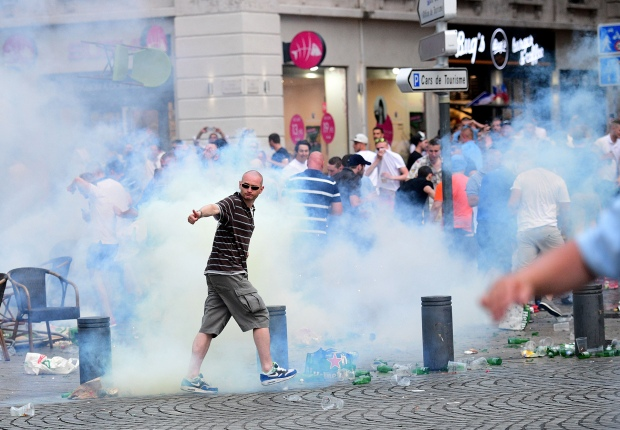 An England fan walks through tear gas released by French police as England fans gather in the port area of Marseille, southern France, on June 10, 2016, ahead of England's Euro 2016 football match against Russia on June 11, 2016. / AFP / LEON NEAL        (Photo credit should read LEON NEAL/AFP/Getty Images)