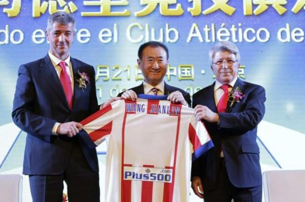 Wang holds an Atletico Madrid jersey with his name, to pose for a photo with Cerezo and Gil after a signing ceremony in Beijing