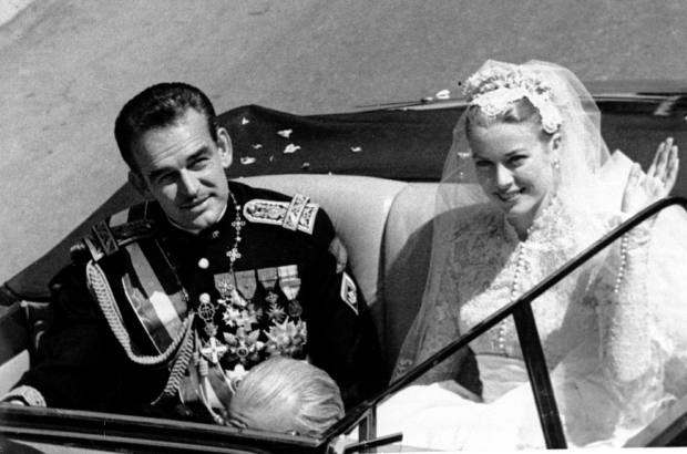 Princess Grace Kelly waves to cheering crowds lining the road as she rides in an open car with Prince Rainier III following their marriage in a religious wedding ceremony in the Monaco Cathedral, in this April 19, 1956 file photo. Many see Rainier's ailing health as the final chapter of a fairy tale romance between an American movie queen and a European prince Friday which has captivated the world , Friday, March 25, 2005 and whose mystique has endured the two decades since her tragic death. (AP Photo)