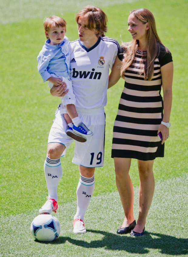 New Real Madrid player Luka Modric from Croatia holds his son beside his wife Vanja, during his official presentation at the Bernabeu stadium in Madrid on Monday, Aug. 27, 2012. Modric passed his routine medical before being presented to a small gathering at the Santiago Bernabeu stadium where he signed a contract to conclude the deal that came at a reported cost of euros 35 million ($44 million) to Madrid.(AP Photo/Daniel Ochoa de Olza)